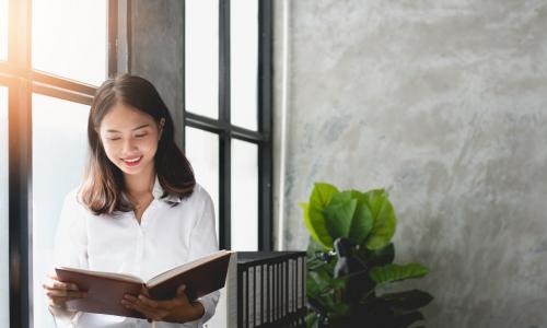 young Asian businesswoman reading by office window