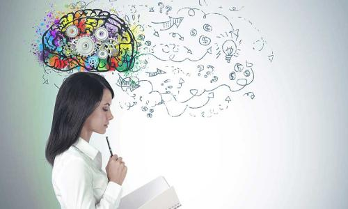 business woman studies a notebook with a colorful brain full of gears above her head