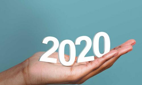 White 2020 year numbers in woman's hand on blue background