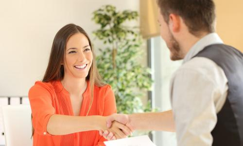 happy front-line credit union employee shakes hands with smiling young woman