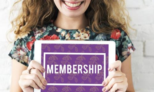 woman holding sign with word membership