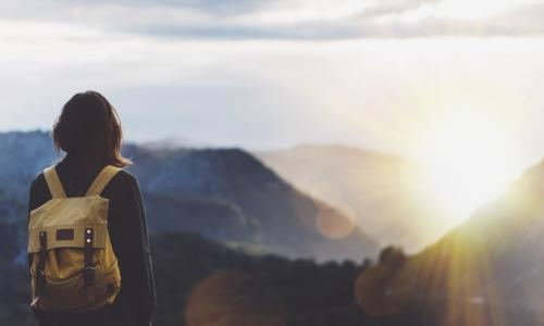 woman with backpack gazing toward sunset over mountain peaks