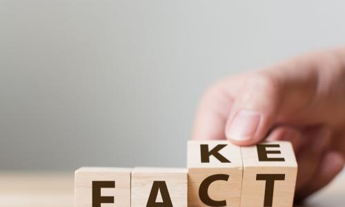 hand flips wooden blocks to change the word fake to spell fact