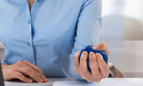 Businesswoman squeezing a blue stress ball in her hand