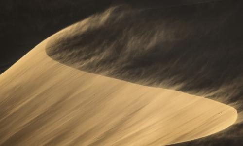 wind blowing across sand dunes