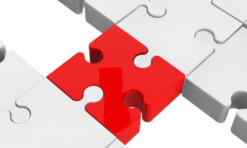 red puzzle piece bridging the gap between two sections of puzzle comprised of white pieces