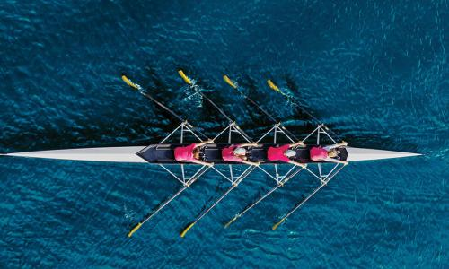 overhead view of rowing crew in red shirts moving through deep blue water
