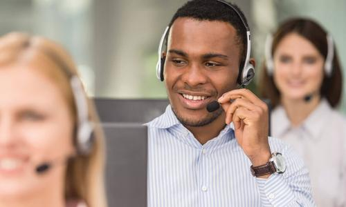 young African American call center employee wearing headset helps customer on phone
