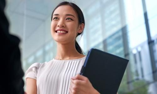 young smiling businesswoman shaking hands after negotiating promotion or job interview