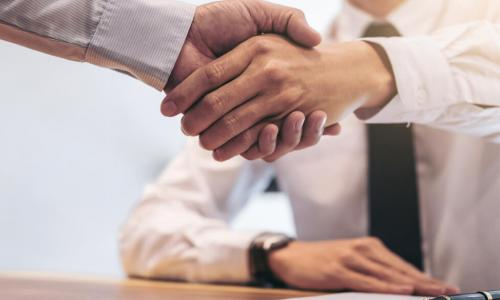 executives shake hands over a contract