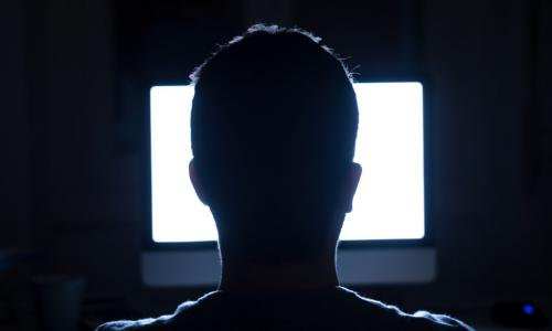 Man sitting in dark in front of bright white computer screen