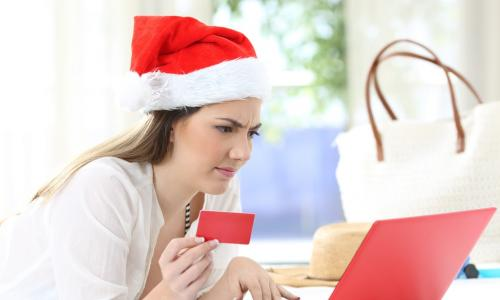 confused woman wearing a Santa hat using credit card with a red laptop