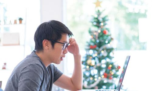 upset young main looks at his finances on laptop with Christmas tree in background