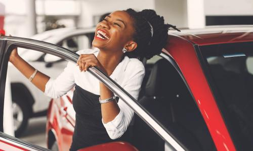 excited young African American woman smiles next to new red car