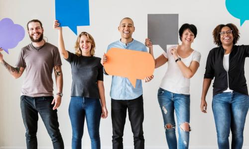 diverse employees standing holding up paper conversation bubbles of different shapes and sizes