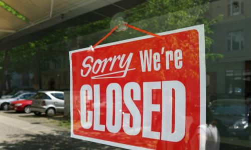 red sign in window of a business that says sorry we're closed
