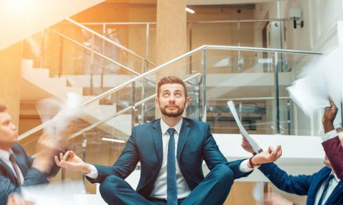 young businessman sits in meditation pose on table while colleagues shout and wave papers at him