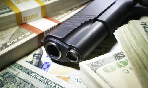 gun on top of money