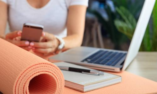 woman with laptop phone and yoga mat