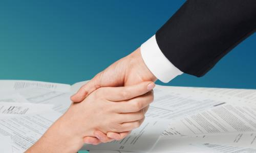 hand of businessperson reaching out to take hand of person drowning in pile of bills and notices