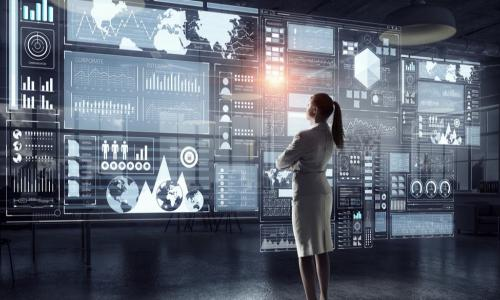 female business leader observing a large holographic display of technology systems