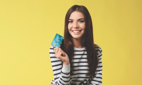 smiling young woman holding new credit card