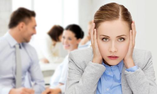 stressed young businesswoman covers her ears in busy office
