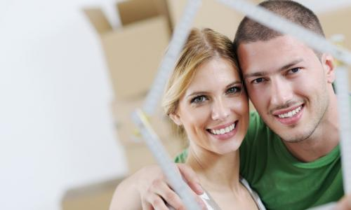 couple look through frame in shape of house