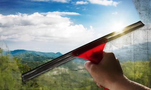 window squeegee washing a window to clear with a beautiful landscape