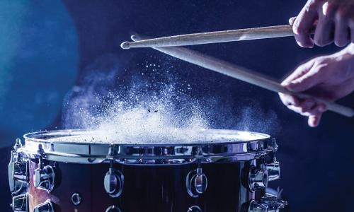 dust puffing upward as drummer hits snare drum with sticks