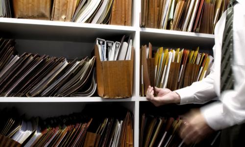 man retrieves old file off shelves