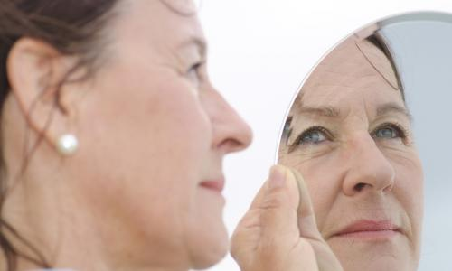 mature woman in pearl earrings looks thoughtfully at her reflection in a hand mirror