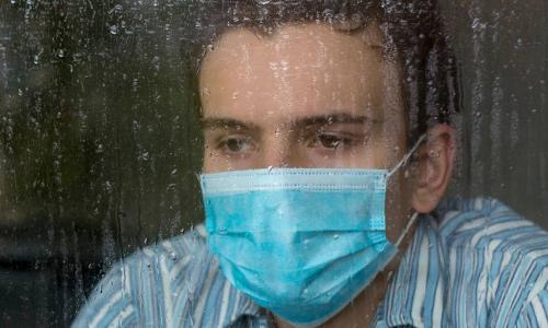 sad man wearing surgical mask looking out window in rain