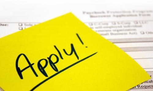 yellow sticky note with the word apply over a paycheck protection program loan application