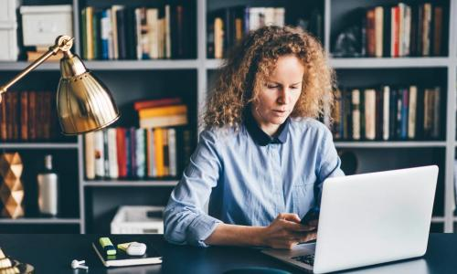 woman learning with laptop and phone in home office library office