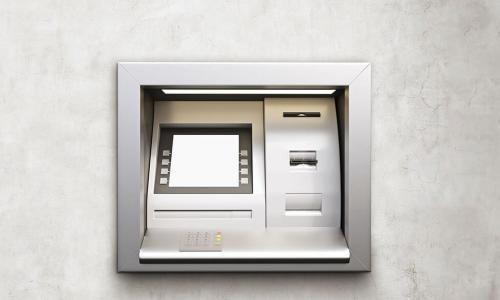 silver ATM on white concrete wall