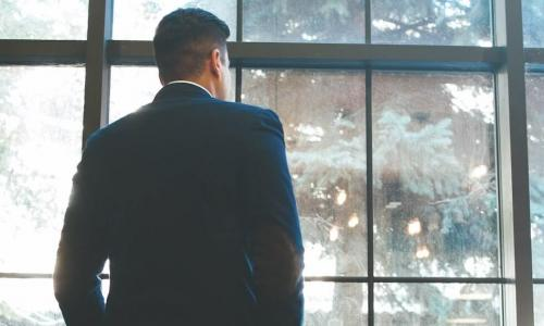 lone businessman in dark suit looks out window to courtyard