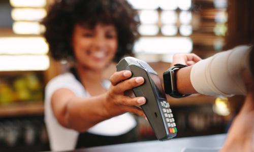 smiling clerk accepts contactless payment via apple watch