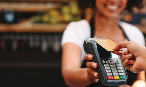 customer taps contactless card on card reader held by clerk