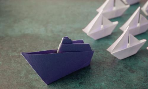 blue origami paper boat leads fleet of smaller white paper boats