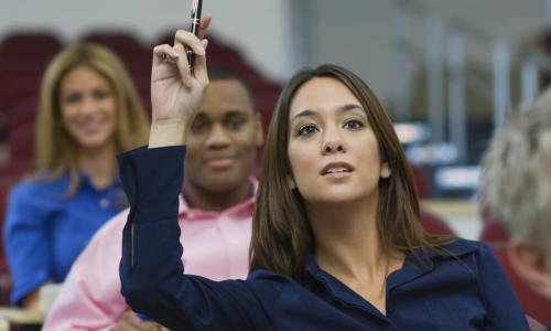 female executive raising hand during training