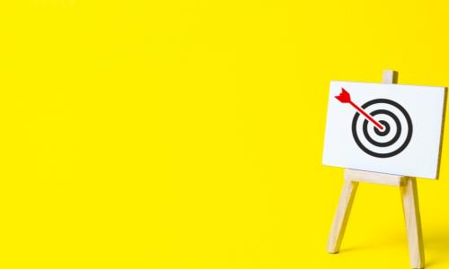 red arrow on target on easel on yellow background
