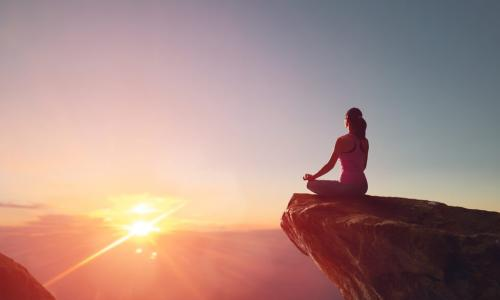woman meditating on rock outcropping at sunrise