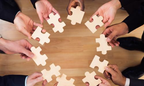 diverse business people put puzzle pieces together
