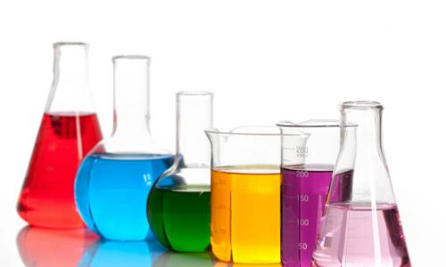 a variety of shaped lab beakers with different color liquid