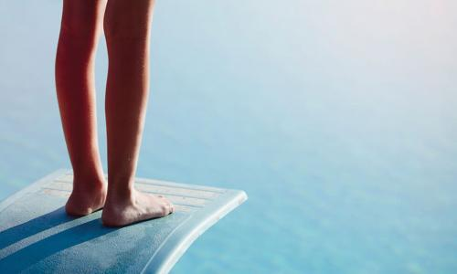 feet of person hesitating near edge of diving board above the water