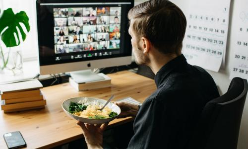 man eating lunch while meeting with colleagues virtually
