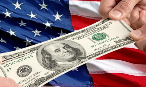 tug of war with 100 dollar bill and a US flag background