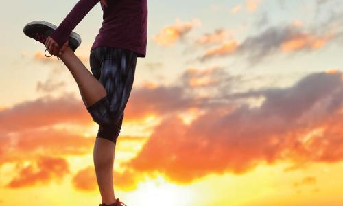 Runner stands on one leg while stretching at sunrise