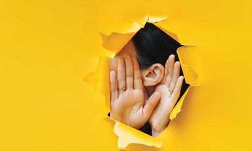 woman holding cupping hands around ear to listen through hole in yellow paper background